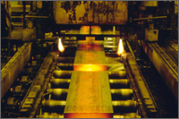 Molten steel continuously cast into large slabs for subsequent rolling and finishing operations