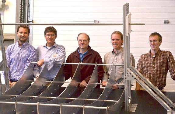 Five men standing behind the metal frame of a CSP receiver.